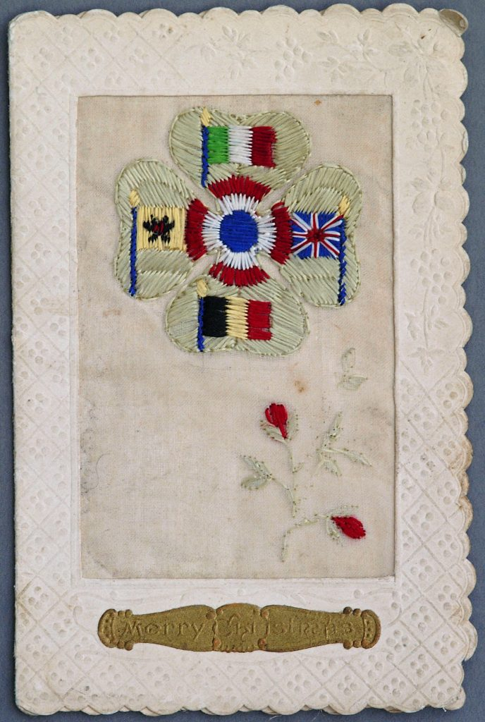 The card shows the flags and colours of five of the Allies on a four-leaf clover; clockwise from the top: Italy, the United Kingdom, Belgium,and Serbia, with the colours of France making up the central roundel. The flowers at the bottom are probably poppies.